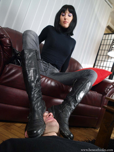 Crushing the slave's face with her boot soles