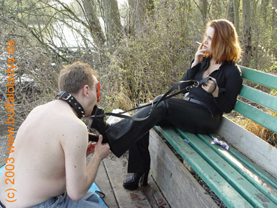 Licking the boot soles of a smoking Mistress