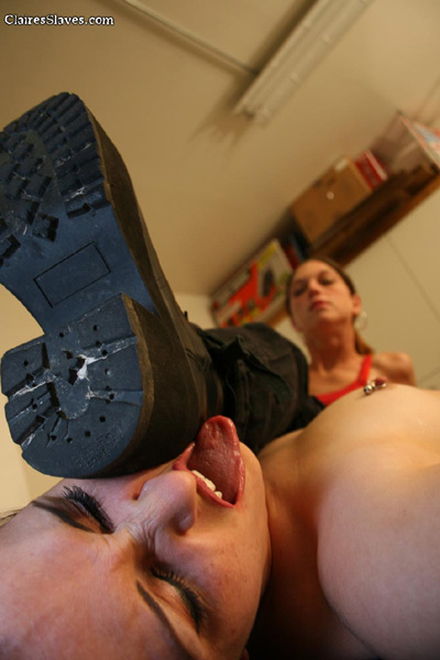 Mistress Claire rests her heavy duty boots on her slave girl's face