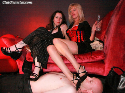 Lady Susana and Mistress Maise resting their foot on the human carpet