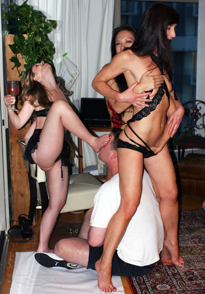 Mistresses having fun with the slave at a party