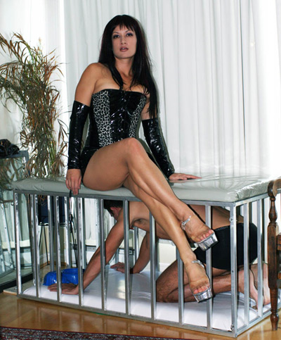 Mistress Jasmine relaxes on top of the slave cage