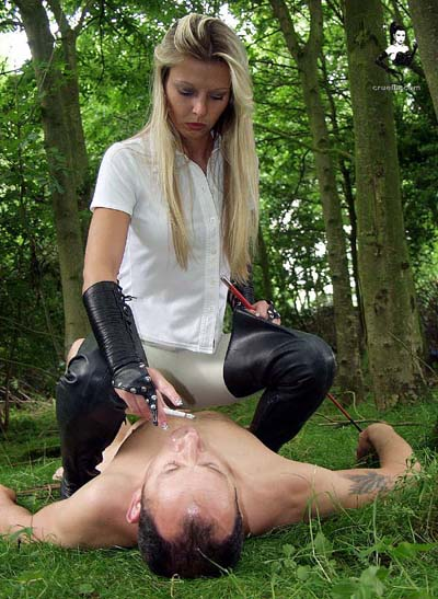 Green loving Mistress taps her ash onto slave