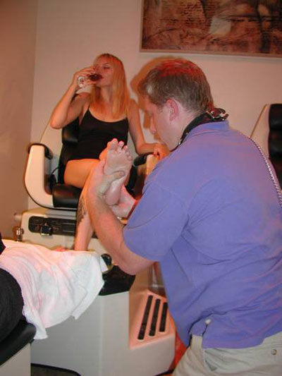 Enjoying wine and a pedicure from her slave