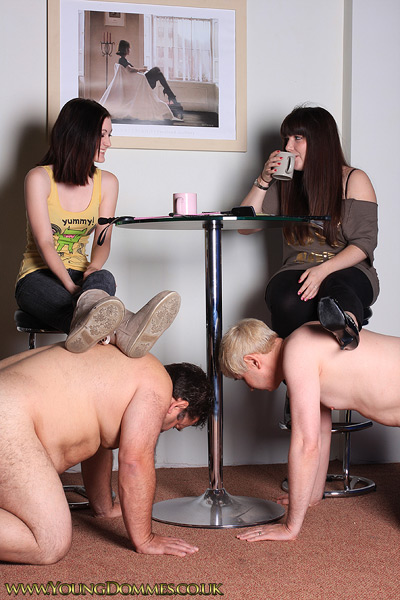 2 slaves serving as foot stools to 2 young Dommes