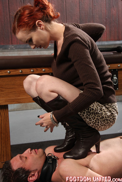 Looking down on the agony of her slave under her boots
