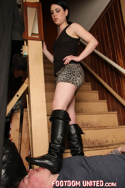 Licking the bottom of her boots at the stairs