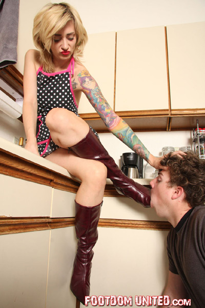 Abusing the mouth of her slave boy with her boots