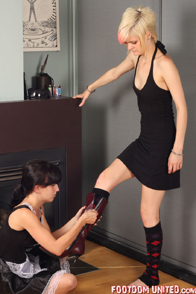 Maid helping Mistress with her boots