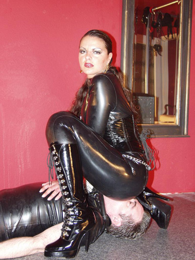 Smothering her slave under her ass in her latex cat suit