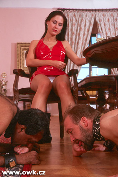 Madame is getting her sweaty feet tasted by 2 slaves