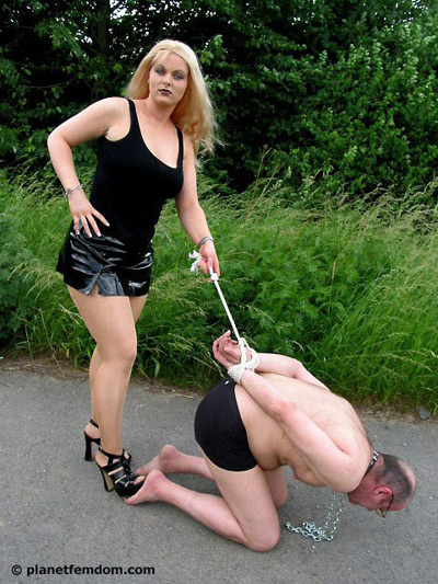 Stepping on the bare feet of her slave with her heels