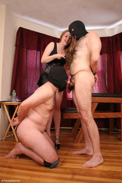 Forcing her slave to suck on another slave