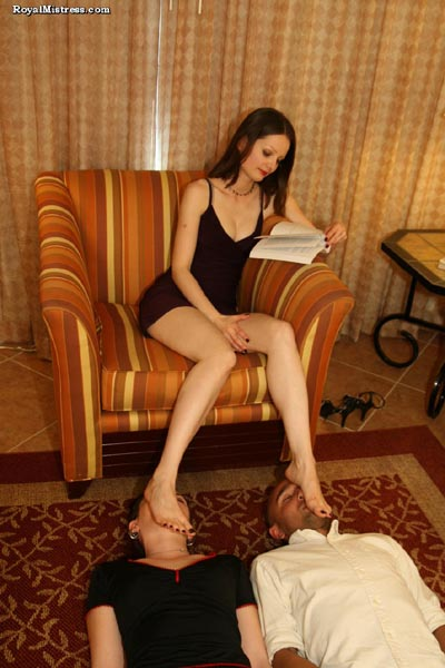 2 faces as Mistress Arella's foot stool while she reads