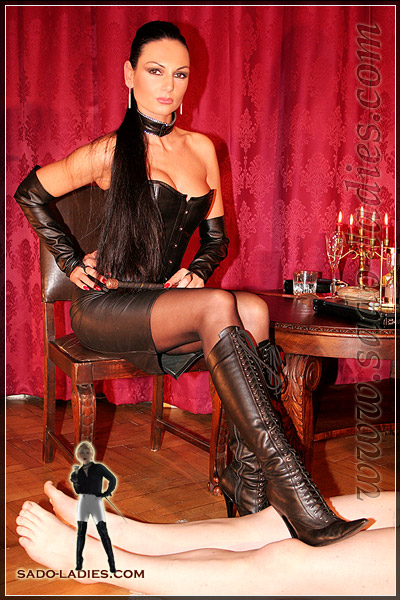 Resting her boots on the legs of her slave