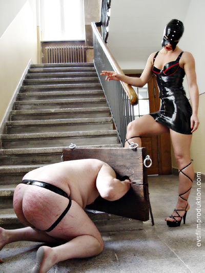 Locked in wooden stocks slave made to kiss on his Mistress's shoes
