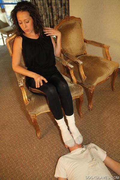 Smothering her smelly gym socks on her slave's face