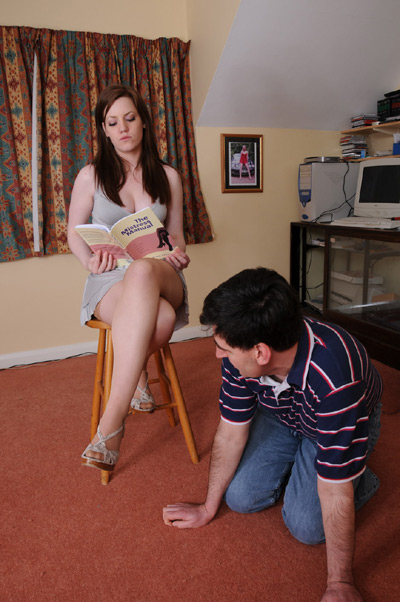 Mistress Zoe reads while her slave kneels beside