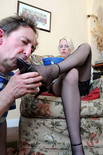 Lady Samantha is reading a magazine while her slave kisses her feet