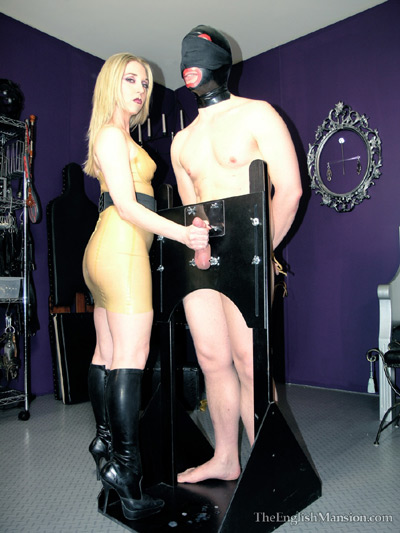 Cock caged in stocks milking by Mistress Sidonia